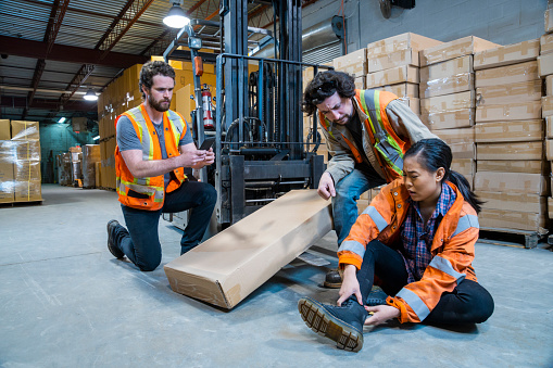 An injured warehouse worker holds her ankle while two co-workers check on her.